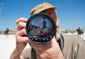 A Man Holds A Camera With A Reflection Of A Young Woman Sitting On A Horse In The Lens