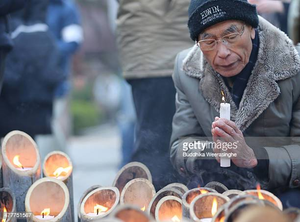 A man holds a candle as he commemorates victims of Great East Japan Earthquake and Tsunami in front of Kobe's light of hope memorial on March 11 2014...