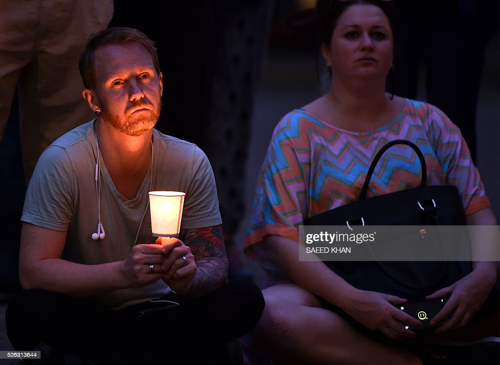 A man holds a candle during a vigil for an Iranian refugee, who died after set himself on fire, in Sydney on April 30, 2016. The 23-year-old known as Omid set fire to himself on April 27, 2016 on the remote Pacific island where he had been sent by Australia, which refuses to resettle boat people even if found to be genuine refugees. / AFP / SAEED
