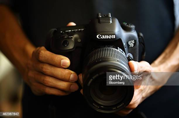 A man holds a Canon Inc digital single lens reflex camera in this arranged photograph in Tokyo Japan on Tuesday Jan 27 2015 Canon the world's largest...