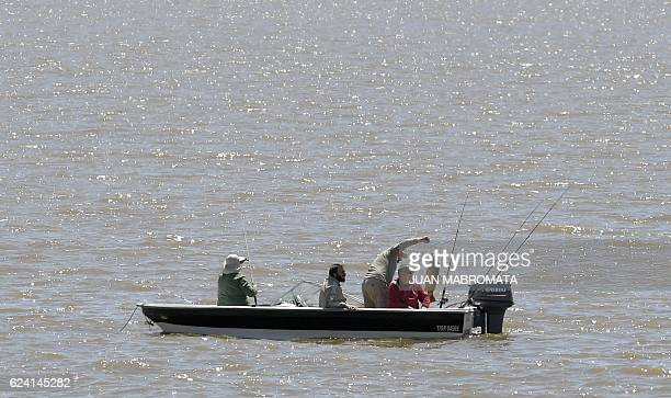 A man holds a carp while fishing from a motorboat in the River Plate in Buenos Aires on November 18 2016 just in front of the 'Parque de la Memoria'...