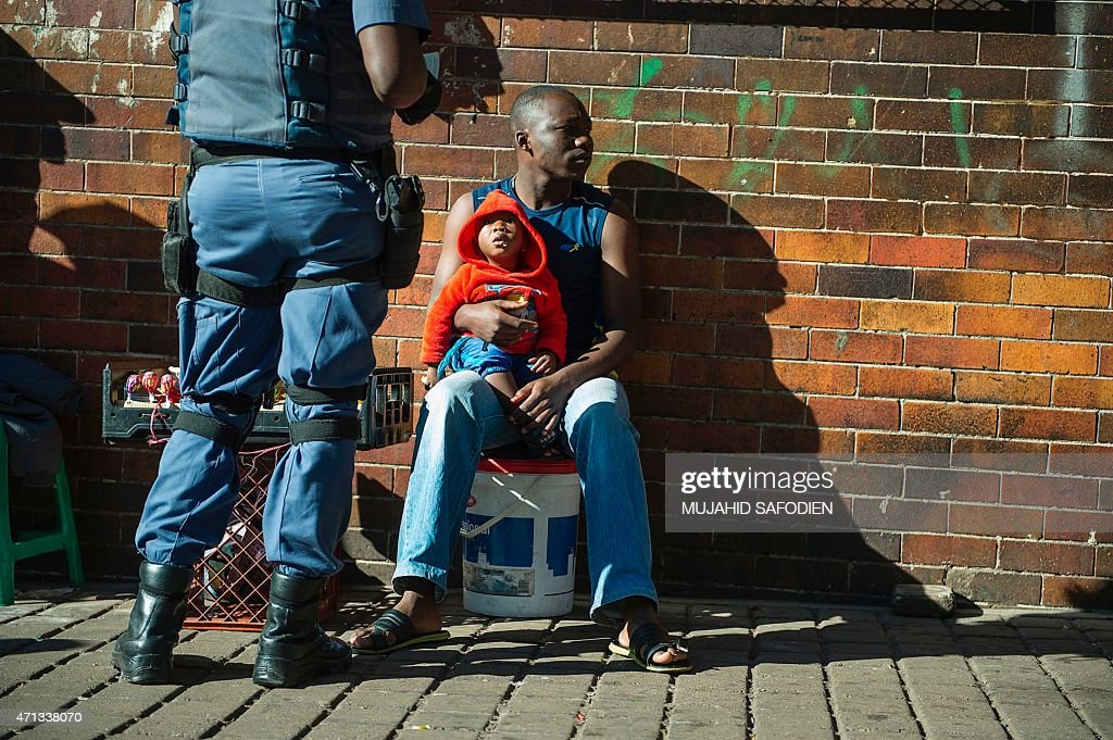 A man holds a child while a police officer check his identity in Hilbrow Johannesburg an area mostly inhabited by foreign nationals on April 27 2015...