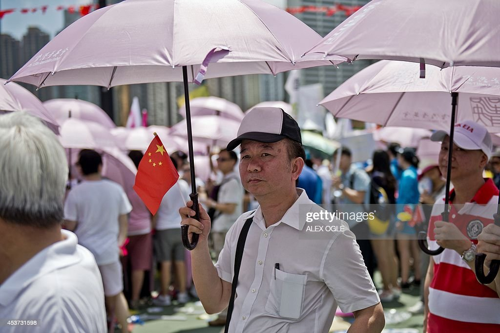 A man holds a Chinese flag and an umbrella as he takes part in a pro-government rally in Hong Kong on August 17, 2014. Thousands protested in Hong Kong on August 17, 2014 against plans by pro-democracy activists to paralyse the city centre with a mass sit-in unless China grants acceptable electoral reforms. AFP PHOTO / ALEX OGLE