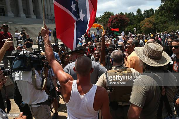 A man holds a Confederate flag during a Black Educators for Justice rally at the South Carolina state house on July 18 2015 in Columbia South...