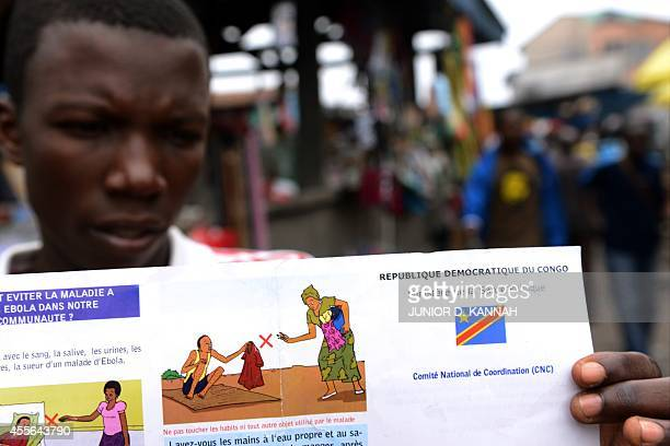 A man holds a Congolese Ministry of Health's information leaflet on Ebola virus on September 17 2014 on Moral's market in the Bandal area in Kinshasa...