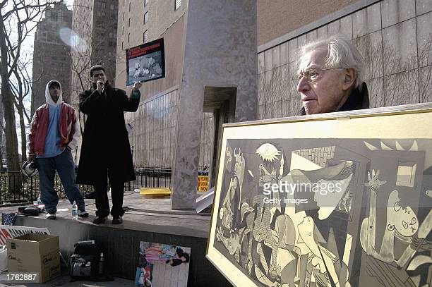A man holds a copy of Picasso's 'Guernica' while standing beside demonstrators in support of US action against Saddam Hussein February 5 2003 outside...