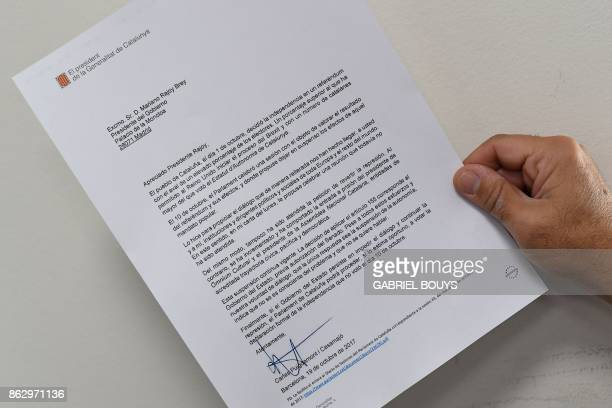 A man holds a copy of the letter sent by Catalan regional government president Carles Puigdemont to Spanish Prime Minister Mariano Rajoy on October...