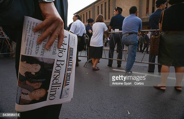 A man holds a copy of the newspaper Giornale di Sicilia which announces the death of antiMafia judge Paolo Borsellino during Borsellino's funeral in...