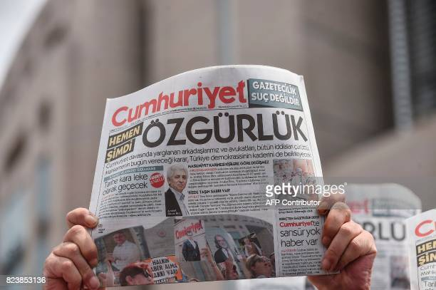 A man holds a copy of today's Cumhuriyet daily newspaper with a word on the frontpage which can be translated as 'Freedom' on July 28 2017 during a...