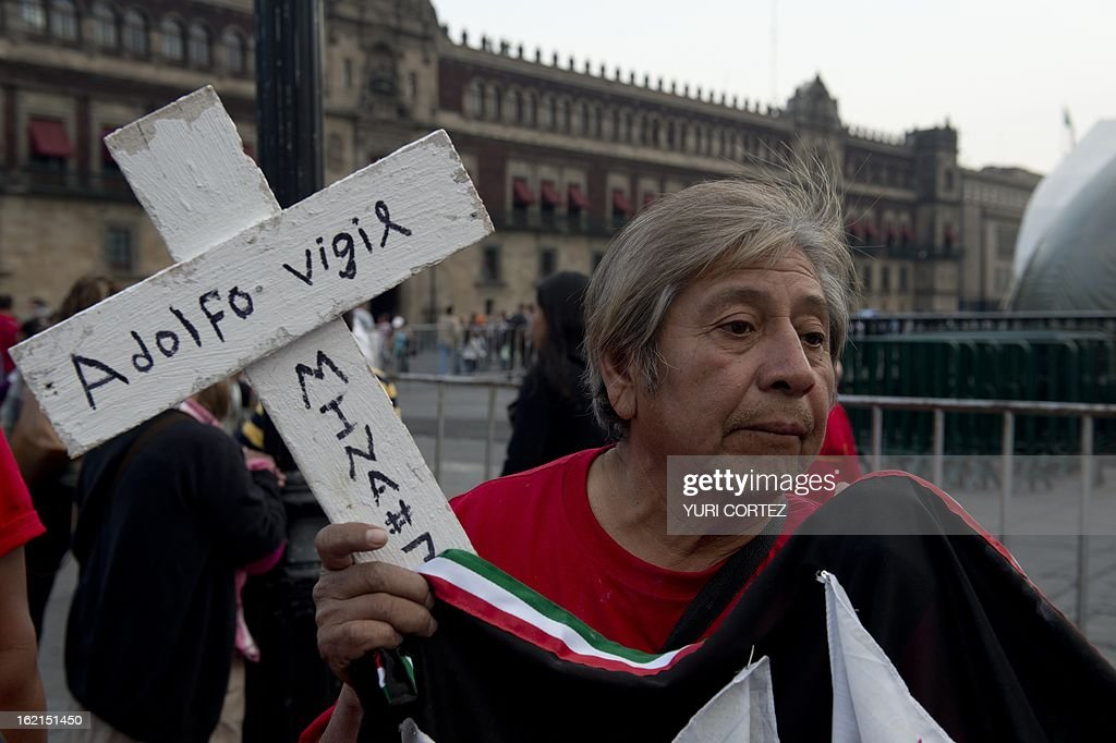A man holds a cross at El Zocalo square in Mexico City, on February 19, 2013, during the commemoration of the 7th anniversary of an accident in which 65 miners were trapped in a coal mine in San Juan de Sabinas, Coahuila state. AFP PHOTO/ Yuri CORTEZ