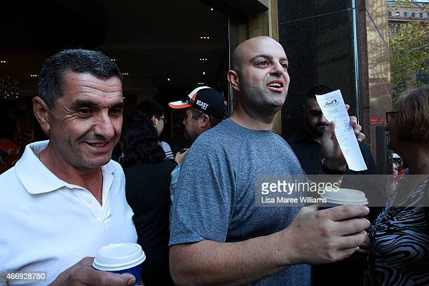 A man holds a docket for the first coffee sold at the Lindt Cafe in Martin Place on March 20 2015 in Sydney Australia The cafe reopened to the public...