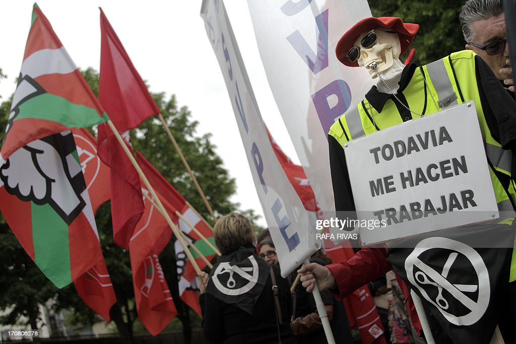 A man holds a doll representing a skeleton holding a placard reading 'They still make me work' during a demonstration by nurses, firemen, teachers, justice workers, police members and other public administration workers in front of Lehendakaritza (Basque government headquarters) against the government's social cuts and austerity policy on June 18, 2013.
