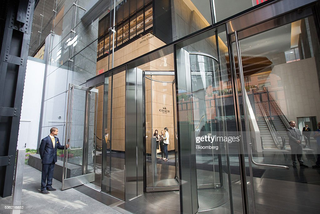 A man holds a door during the opening of Coach Inc.'s new offices at 10 Hudson Yards in New York, U.S., on Tuesday, May 31, 2016. The first skyscraper at Related Cos.'s $25 billion Hudson Yards project opened Tuesday after three and a half years of construction, bringing office workers to a once-desolate area of Manhattan's far west side that's now transforming into a new business enclave. Photographer: Michael Nagle/Bloomberg via Getty Images