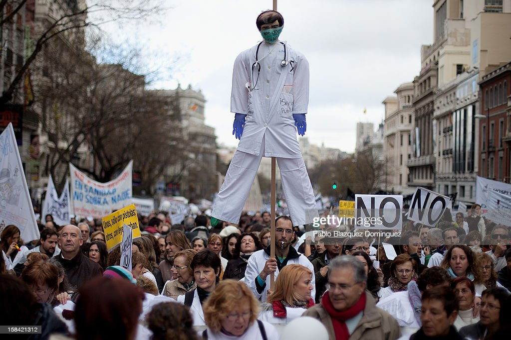 A man holds a dummy depicting a health worker amid other health workers during a demonstration against cuts on public health care and the privatization of medical centers and hospitals on December 16, 2012 in Madrid, Spain. In Madrid, doctors have already staged 11 days of strikes and all health workers unions are calling for a third 48 hour strike on December 19 and December 20. Around 4,000 operations have been suspended in Madrid since the medical strikes started.