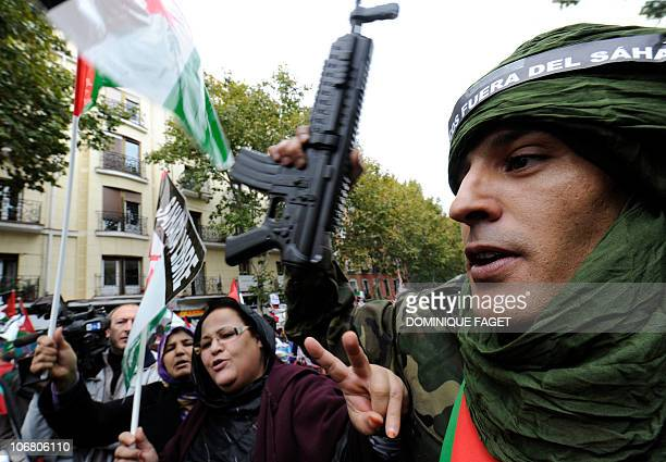 A man holds a fake gun on November 13 2010 during a demonstration in Madrid to condemn a deadly Moroccan raid on a camp in the disputed Western...