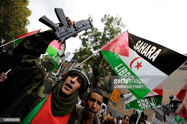 A man holds a fake machine gun on November 13 2010 during a demonstration in Madrid to condemn a deadly Moroccan raid on a camp in the disputed...