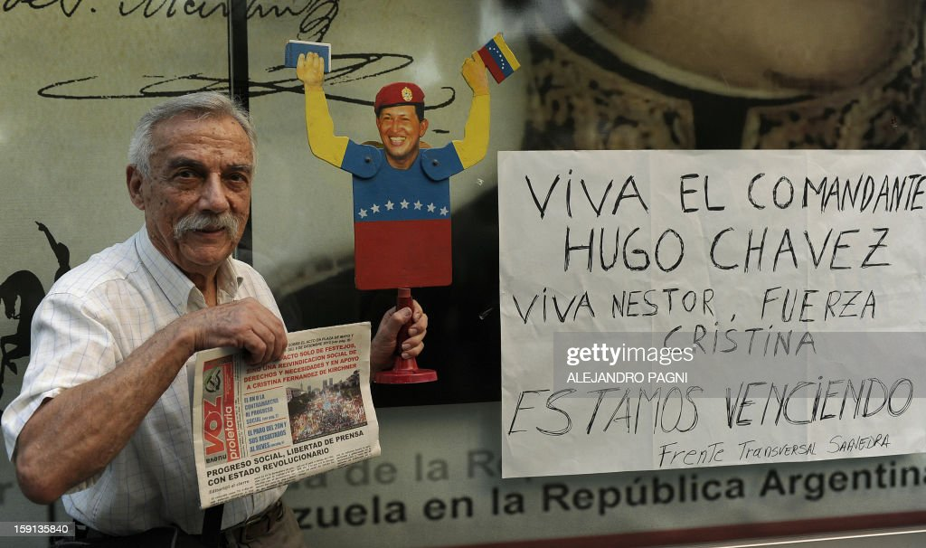 A man holds a figurine of Venezuelan President Hugo Chavez during a rally in support of his recovery in front of the Venezuelan embassy in Buenos Aires on January 8, 2013. The President of the National Assembly Diosdado Cabello announced today that due to health reasons, Chavez will not be able to take the oath to be sworn in for a fourth term in office next January 10. A constitutional fight intensified with the government planning a massive show of support in the streets on the day he is supposed to be sworn in. Chavez, who underwent his fourth round of cancer surgery in Havana nearly a month ago, is suffering from a severe pulmonary infection that has resulted in a respiratory insufficiency. The sign reads 'Long live Commander Chavez. Long live Nestor (Kirchner), Strength Cristina (Fernandez). We are overcoming'. AFP PHOTO / ALEJANDRO PAGNI