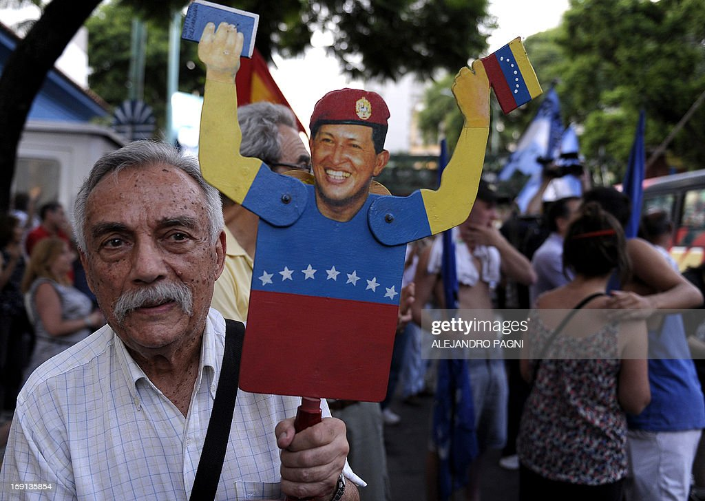 A man holds a figurine of Venezuelan President Hugo Chavez during a rally in support of his recovery in front of the Venezuelan embassy in Buenos Aires on January 8, 2013. The President of the National Assembly Diosdado Cabello announced today that due to health reasons, Chavez will not be able to take the oath to be sworn in for a fourth term in office next January 10. A constitutional fight intensified with the government planning a massive show of support in the streets on the day he is supposed to be sworn in. Chavez, who underwent his fourth round of cancer surgery in Havana nearly a month ago, is suffering from a severe pulmonary infection that has resulted in a respiratory insufficiency. AFP PHOTO / ALEJANDRO PAGNI