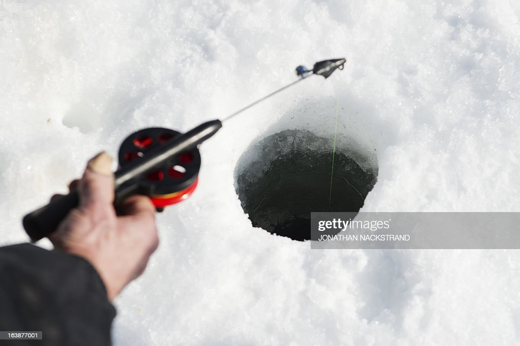 A man holds a fishing pole into a hole on the frozen Oster-Jansjon lake as he participate in an ice fishing contest in Are, Sweden on March 17, 2013.