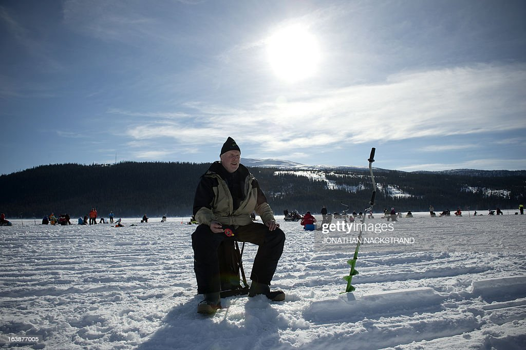 A man holds a fishing pole into a hole on the frozen Oster-Jansjon lake as he participates in an ice fishing contest in Are, Sweden on March 17, 2013.