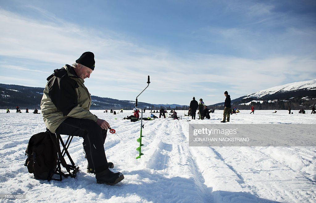 A man holds a fishing pole into a hole on the frozen Oster-Jansjon lake as he participates in an ice fishing contest in Are, Sweden on March 17, 2013. AFP PHOTO/JONATHAN NACKSTRAND