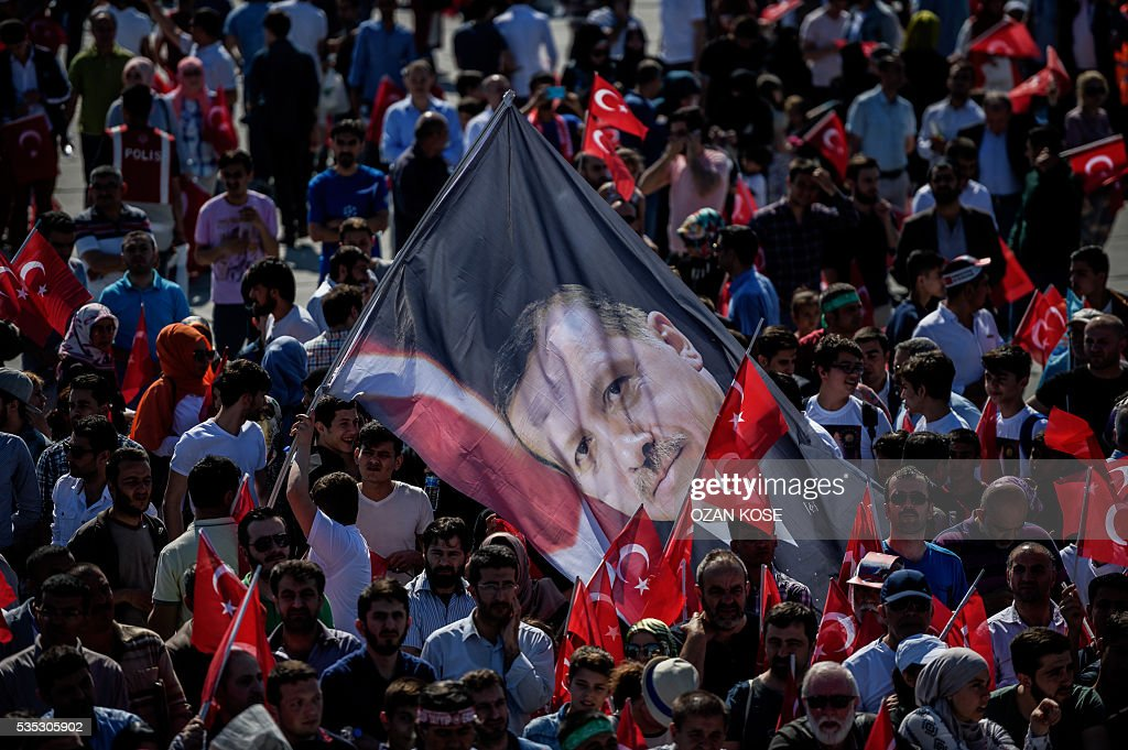 A man holds a flag bearing a picture of Turkish President Recep Tayyip Erdogan during a rally to mark the 563rd anniversary of the conquest of Istanbul by Ottoman Turks on May 29, 2016 in Istanbul. / AFP / OZAN