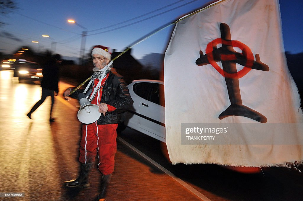 A man holds a flag during a demontration which gathers about 300 opponents to the project of an international airport in Notre-Dame-des-Landes in support of two activists who are incarcerated at the Nantes-Carquefou prison, on December 29, 2012 in Nantes, western France.