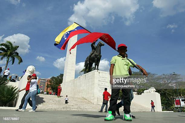 A man holds a flag during the march of the supporters of President Hugo Chavez through the streets of Caracas to the military academy on March 06...