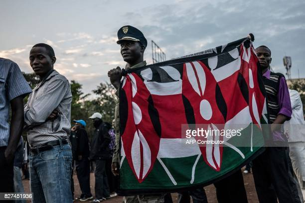 A man holds a flag in the colours of the Kenyan national flag as he and others wait in line to cast their ballot in the general elections at a...