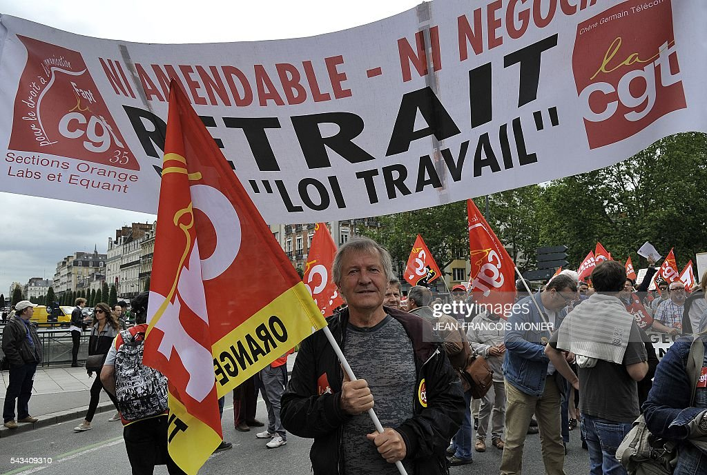 A man holds a flag of a French union as a banner reads 'Withdraw labour law' during a demonstration against controversial labour reforms, on June 28, 2016 in Rennes. Unions have called repeated strikes and marches in opposition to the law, which seeks to bring down France's intractable 10-percent unemployment rate by making it easier to hire and fire workers. / AFP / JEAN