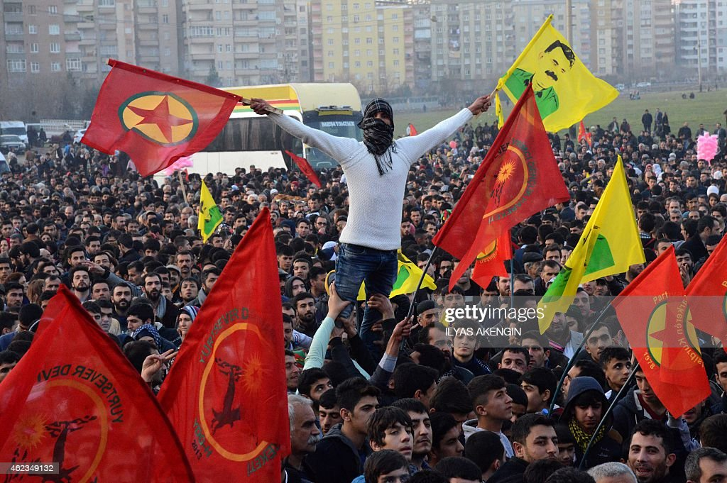 A man holds a flag of the Kurdish Worker's Party (PKK) and a poster flag of jailed kurdish leader and PKK founder Abdullah Ocalan during a rally on January 27, 2015 in Diyarbakir, southeastern Turkey, following news that Kurdish fighters drove the Islamic State group from the Syrian border town of Kobane, also known as Ain al-Arab, which became a major symbol of resistance against the jihadists.