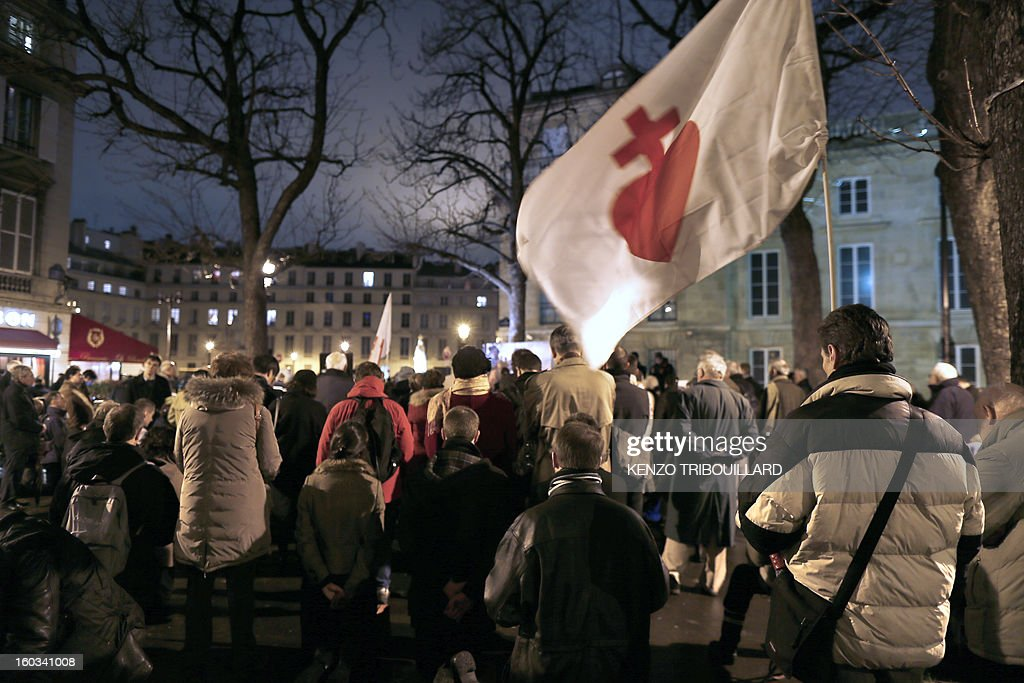 A man holds a flag with a sacred heart as people kneel during a protest organized by fundamentalist Christians group Civitas Institute against same-sex marriage on January 29, 2013 in Paris. France's parliament began today examining draft legislation on same-sex marriage after months of rancorous debate and huge street protests by both supporters and opponents. AFP PHOTO / KENZO TRIBOUILLARD