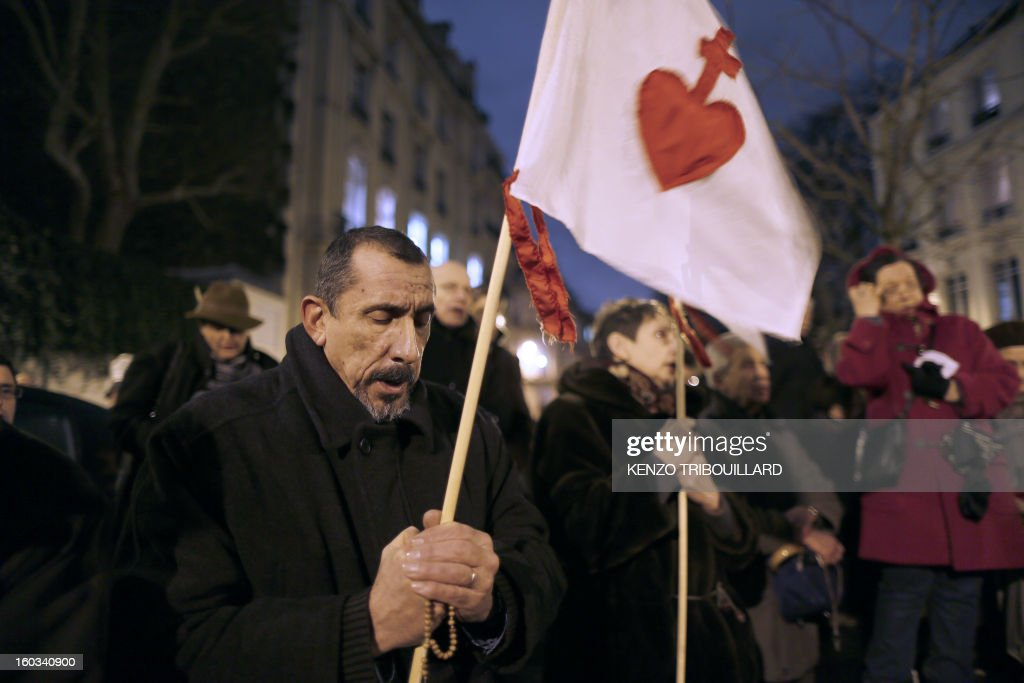 A man holds a flag with a sacred heart as people pray during a protest organized by fundamentalist Christians group Civitas Institute against same-sex marriage on January 29, 2013 in Paris. France's parliament began today examining draft legislation on same-sex marriage after months of rancorous debate and huge street protests by both supporters and opponents.