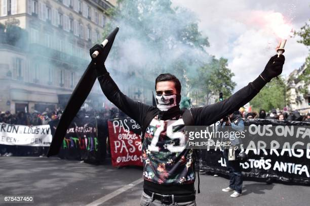 TOPSHOT A man holds a flags and smoke flare as he leads a march during the protest for the annual May Day workers' rally in Paris on May 1 2017 / AFP...