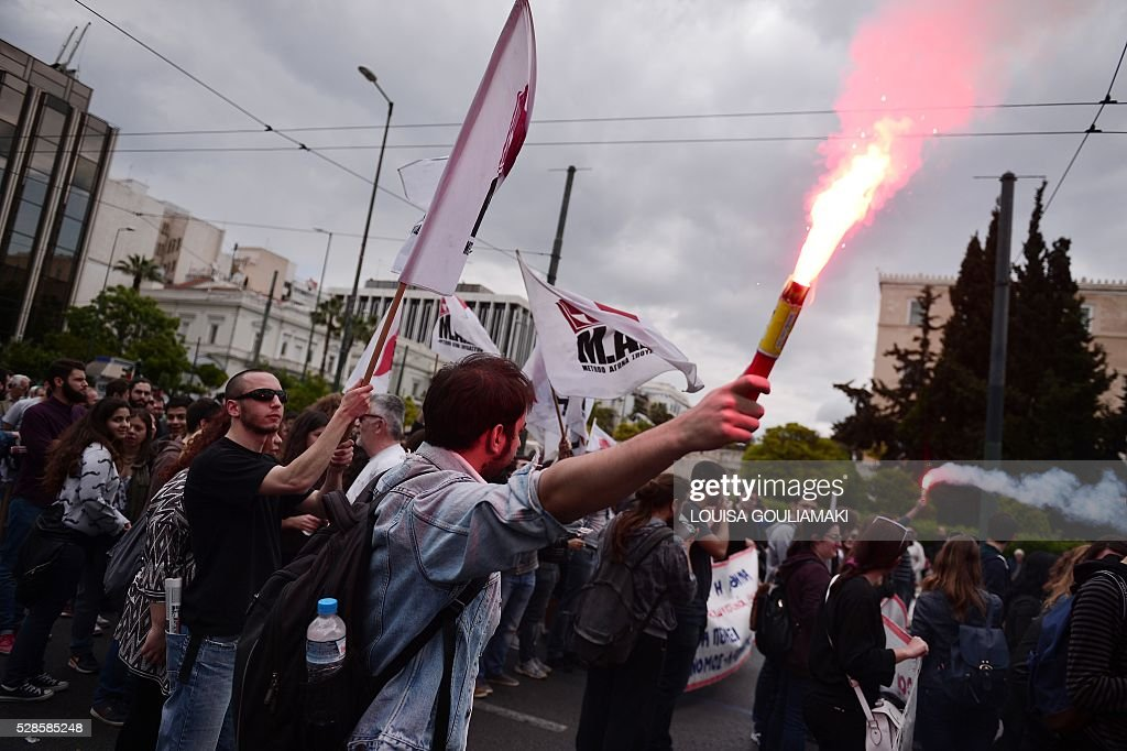 A man holds a flare during a demonstration in front of the Greek parliament in Athens, as part of a 48-hour general strike to protest controversial government plans to overhaul pensions and increase taxes to meet demands of its bailout creditors , on May 6, 2016. / AFP / LOUISA