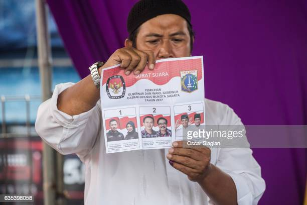 A man holds a flier as he attends the vote count for the Jakarta Governor election on February 15 2017 in Jakarta Indonesia Residents of Indonesia's...