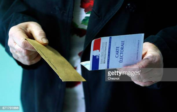 A man holds a French voter registration card and an envelopp with his ballot during the first round of 2017 French presidential election at a polling...