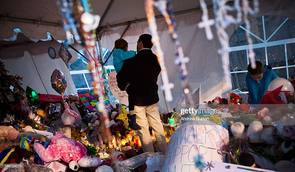 A man holds a girl in his arms while silently observing a memorial for those killed in the school shooting at Sandy Hook Elementary School on December 24, 2012 in Newtown, Connecticut. Donations and letters are pouring in from across the country as the town tries to recover from the massacre.