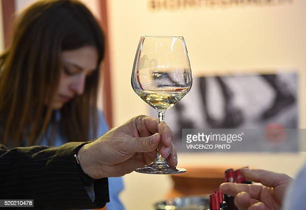 A man holds a glass of wine on April 10 2016 during the 50th edition of the Vinitaly wine exhibition in Verona Vinitaly is the worlds largest wine...