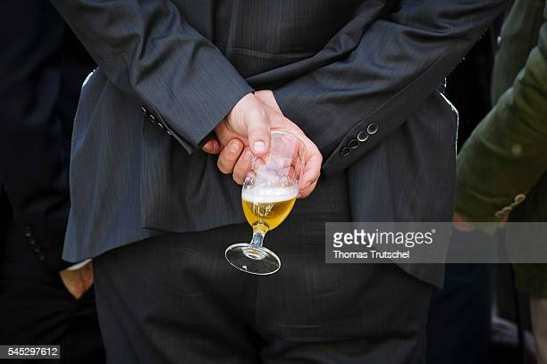 A man holds a glass with beer behind his back on July 06 2016 in Berlin Germany