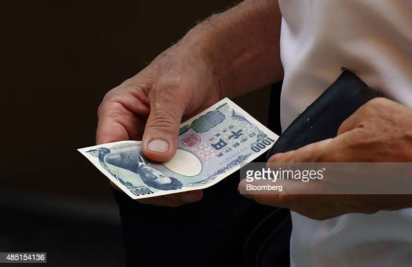 A man holds a Japanese 1000 yen banknote as he shops at a store in Tokyo Japan on Tuesday Aug 25 2015 The yen fell against the dollar for the first...