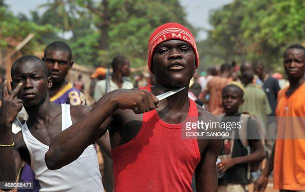 A man holds a knife to his throat claiming that he is looking for Muslims to cut off their heads in the 5th district of Bangui on February 9 2014...