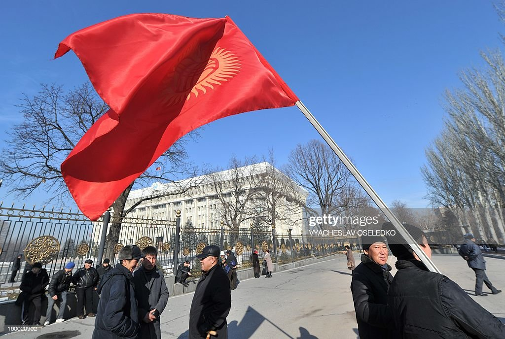 A man holds a Kyrgyz flag during a rally of the relatives of those who were killed during the April 2010 uprising that ousted president Kurmanbek Bakiyev and installed a new government pray during a rally just outside the government headquarters in the Kyrgyzstan's capital Bishkek on January 24, 2013. The rally participants demanded today the arrest of all those responsible for the April 2010 killings.