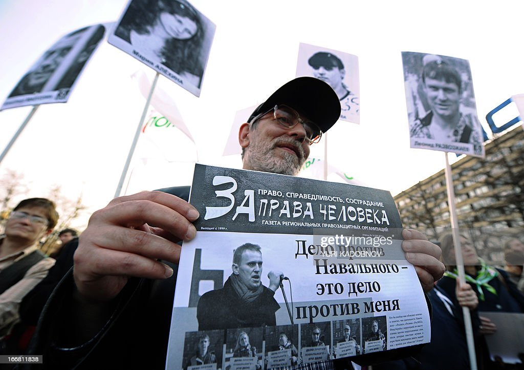 A man holds a leaflet reading 'For human rights' with a picture of Russian protest leader Alexei Navalny during an opposition rally in his support in central Moscow on April 17, 2013.Russian opposition leader Alexei Navalny went on trial Wednesday on charges he says were ordered by President Vladimir Putin to eliminate a top opponent, but the process was swiftly adjourned for a week to allow the defence more time to prepare.