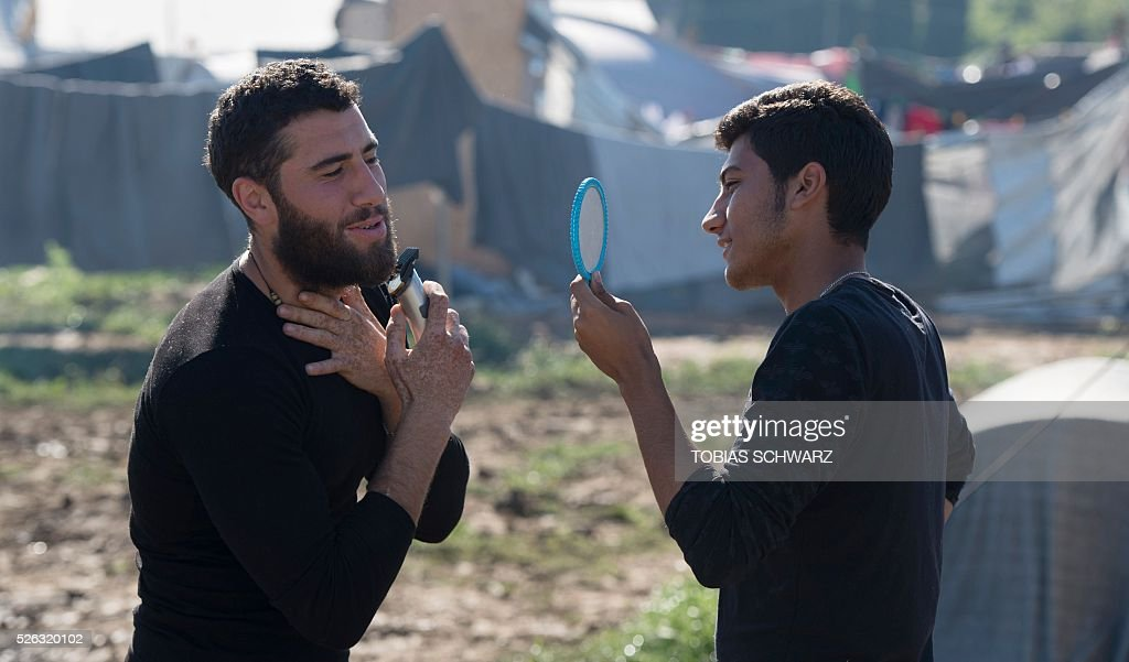 A man holds a mirror up for another as he uses an electric shaver at a makeshift camp for migrants and refugees near the village of Idomeni, not far from the Greek-Macedonian border, on April 30, 2016. Some 54,000 people, many of them fleeing the war in Syria, have been stranded on Greek territory since the closure of the migrant route through the Balkans in February. / AFP / TOBIAS