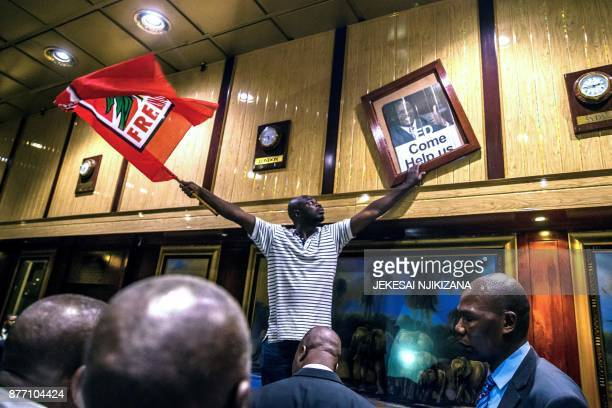 TOPSHOT A man holds a Mozambican Liberation Movement flag and a poster with the portrait of former Zimbabwean deputy President Emmerson...