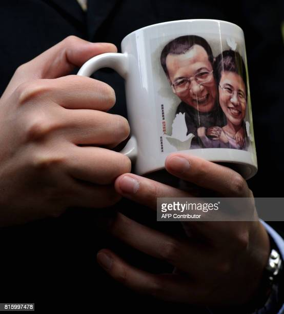 A man holds a mug bearing a picture of mainland jailed dissident Liu Xiaobo and his wife Liu Xia outside the legislative council in Hong Kong on...