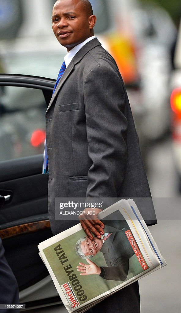 A man holds a newspaper reading 'Goodbye Tata' outside the home of South African president Nelson Mandela in Johannesburg on December 6, 2013 where he died the day before. Mandela, the revered icon of the anti-apartheid struggle in South Africa and one of the towering political figures of the 20th century, has died aged 95. Mandela, who was elected South Africa's first black president after spending nearly three decades in prison, had been receiving treatment for a lung infection at his Johannesburg home since September, after three months in hospital in a critical state.
