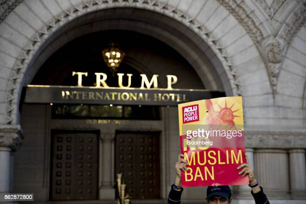 A man holds a 'No Muslim Ban' sign near the Trump International Hotel during a protest in Washington DC US on Wednesday Oct 18 2017 Today a federal...