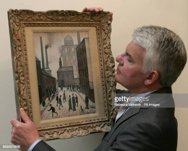 A man holds a painting by Laurence Stephen Lowry entitled Street Scene 1953 is on display at Chelsea Art Fair The painting belongs to Neptune Fine...